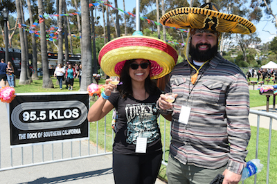 Sombrero-clad Sabroso attendees enjoying craft beer samples in front of a KLOS banner