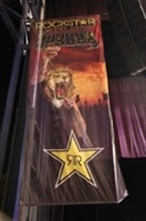 Rockstar Main Stage banner, featuring an image of a lion's head on a male singer's body, fist pumped in the air, in front of a fiery backdrop. Photo by Strati Hovartos.